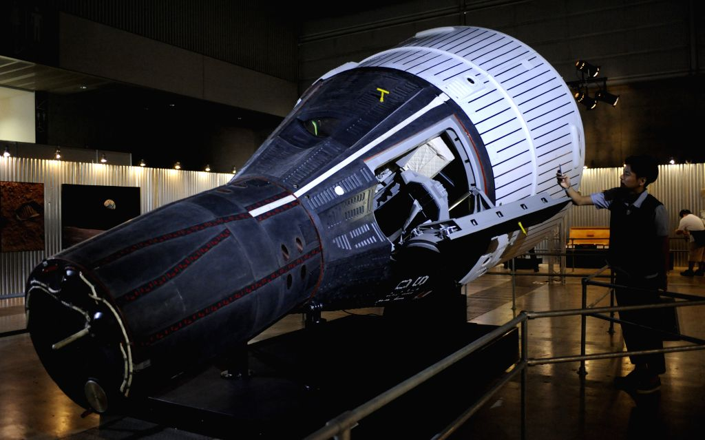 "A man takes pictures of a replica of the Gemini Spacecraft during a press preview of ""SPACE EXPO 2014"" at Makuhari Messe in Chiba prefecture, east of Tokyo,"