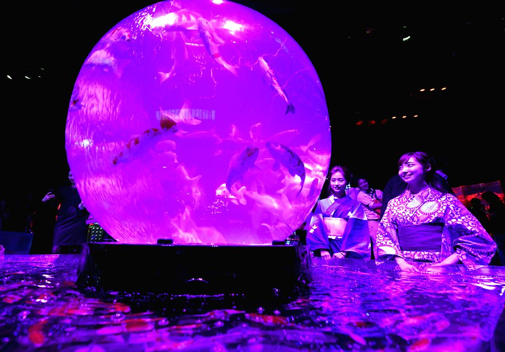 TOKYO, July 5, 2018 - Women look at an installation with goldfish in illuminated tanks at Art Aquarium exhibition in Tokyo, Japan, July 5, 2018.