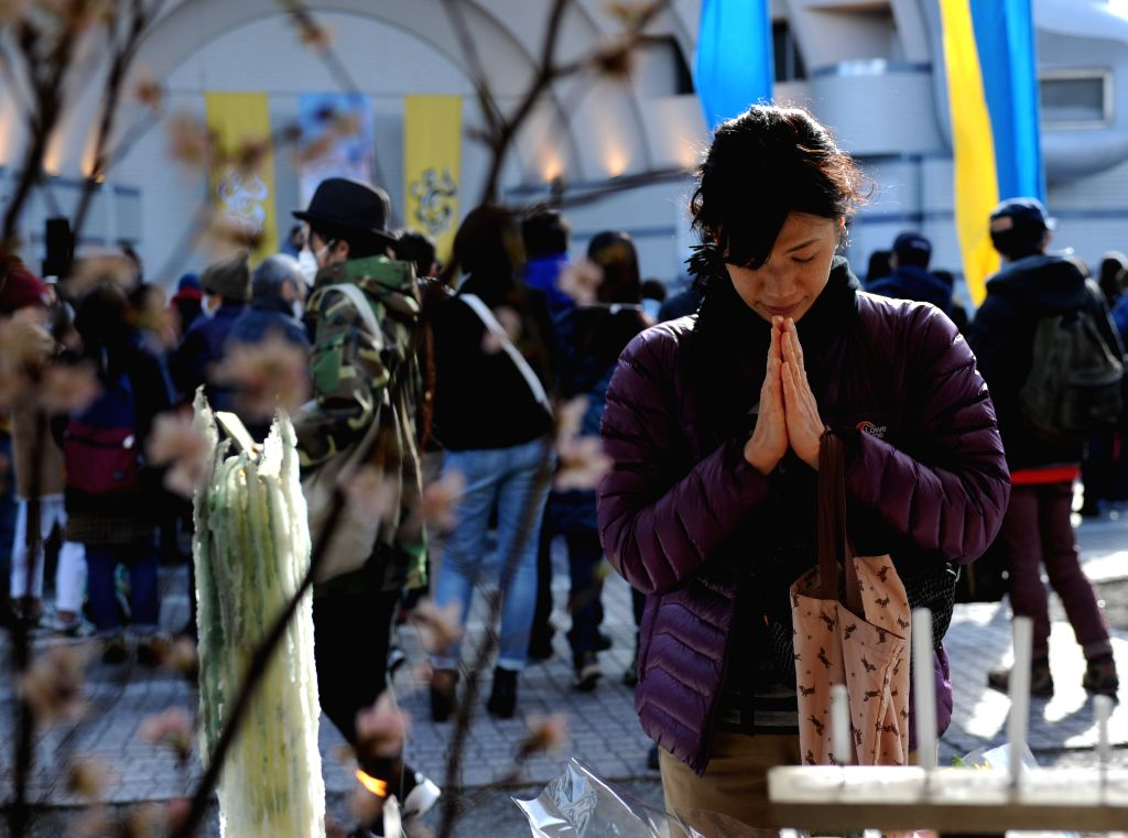 A woman offers prayers during a memorial service marking the 4th anniversary of the 2011 earthquake and tsunami that pummeled the eastern sea board and left more ...