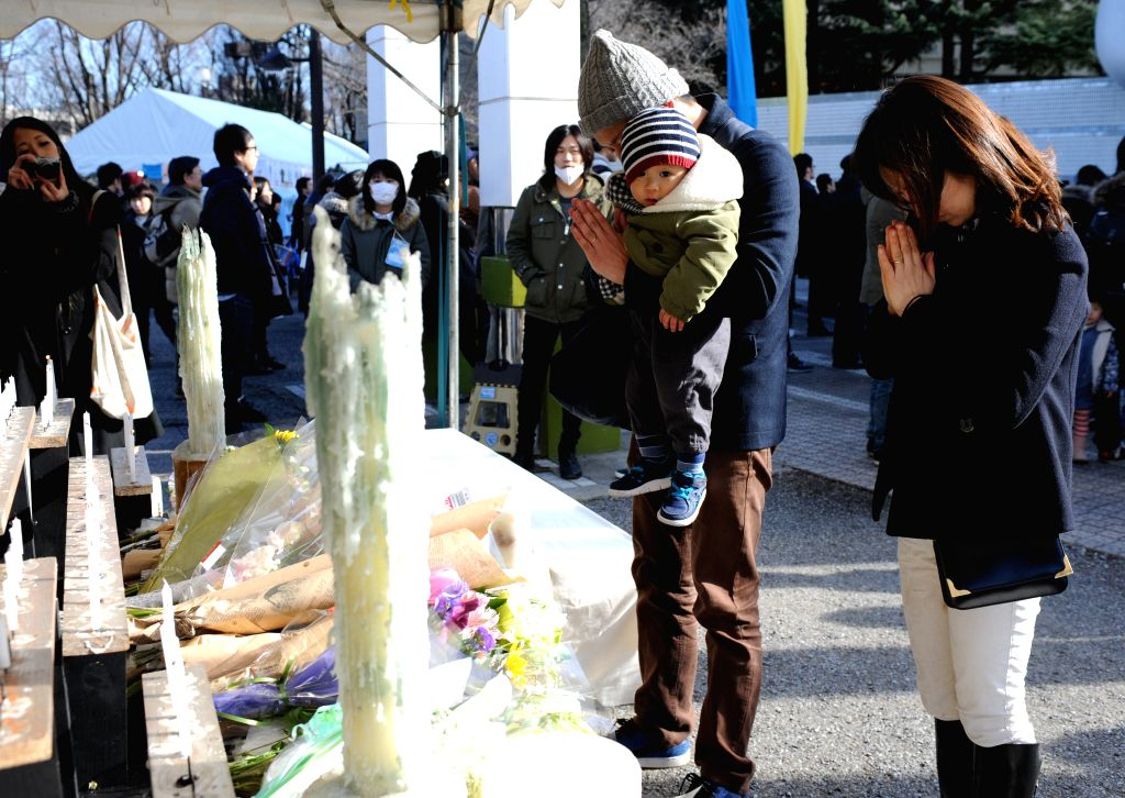 People offer prayers during a memorial service marking the 4th anniversary of the 2011 earthquake and tsunami that pummeled the eastern sea board and left more than ...