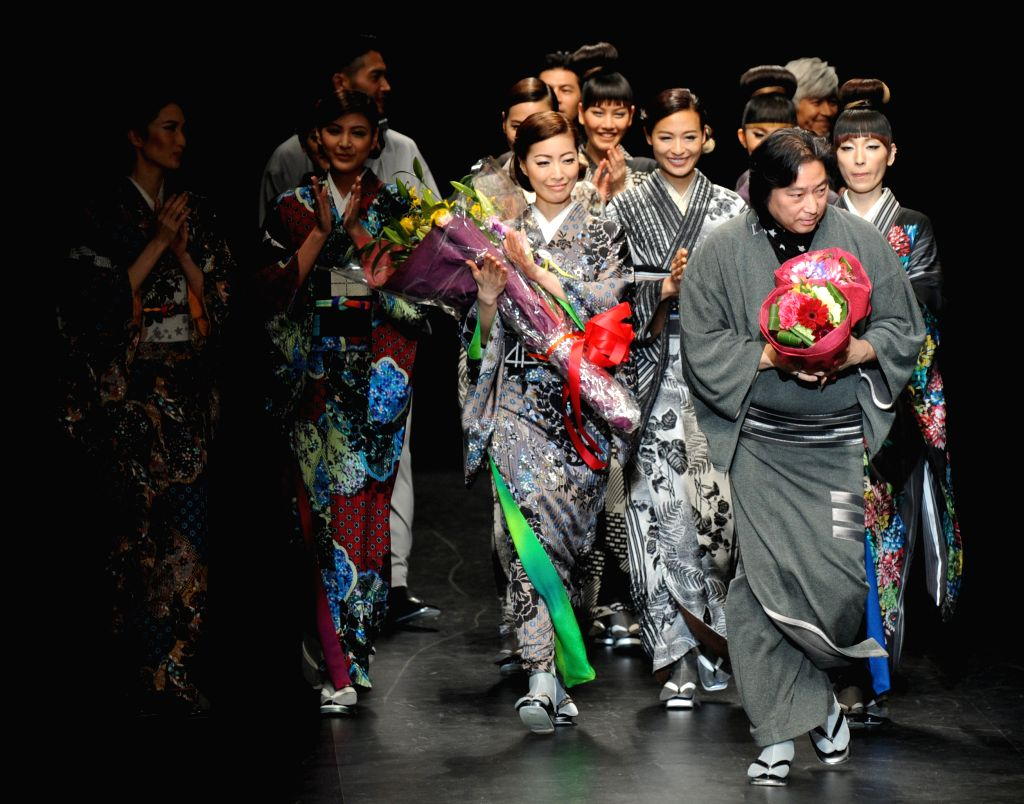 Fashion designer Joaro Saito (front) walks the runway with models during his 2015-16 Autumn/Winter Collection at a fashion week in Tokyo, Japan, March 19, 2015. ...