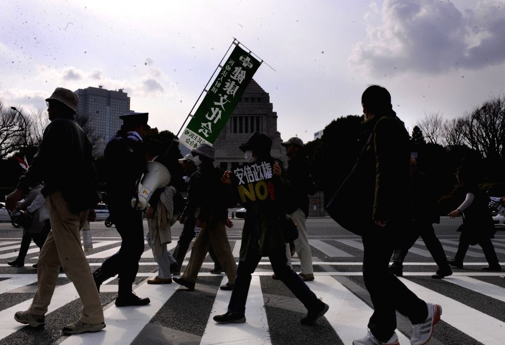 People walk to attend a demonstration against Japanese Prime Minister Shinzo Abe in Tokyo, Japan, March 22, 2015. - Shinzo Abe