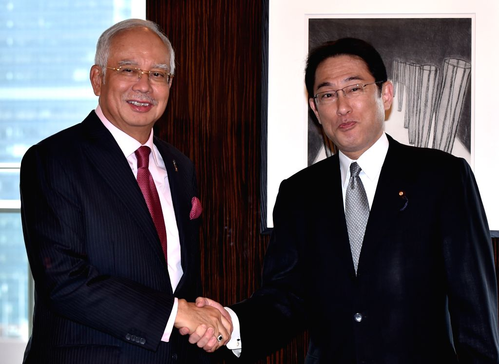 Japanese Foreign Minister Fumio Kishida (R) shakes hands with visiting Malaysian Prime Minister Najib Razak during their meeting in Tokyo, capital of Japan, on May 25, ... - Fumio Kishida