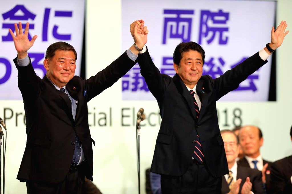 TOKYO, Sept. 20, 2018 - Japanese Prime Minister Shinzo Abe and former Defense Minister Shigeru Ishiba (L) raise their hands during the ruling Liberal Democratic Party (LDP) leadership election in ... - Shinzo Abe