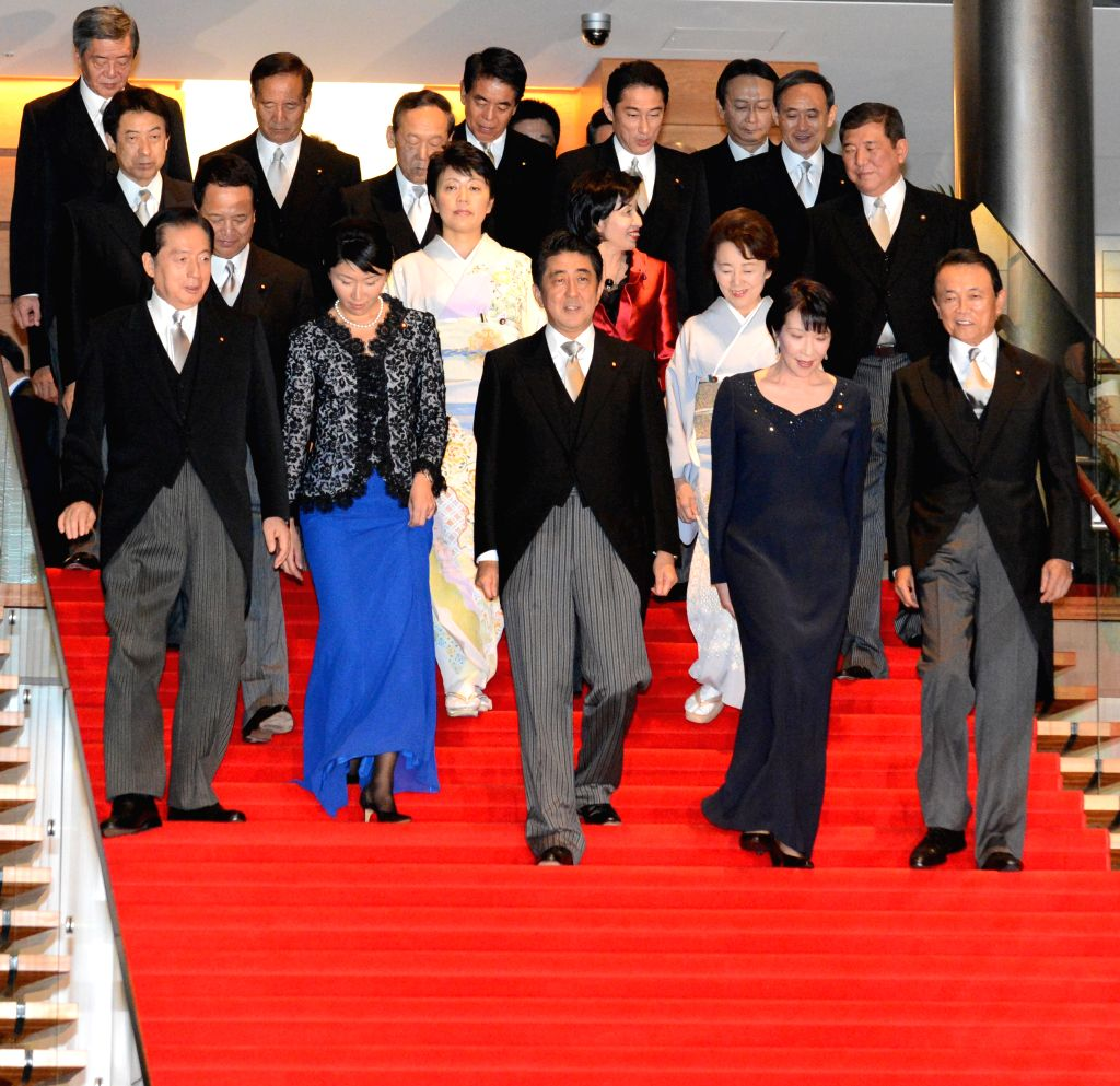 Japan's Prime Minister Shinzo Abe (C, front) and other members of the new Cabinet pose for a group photo at the prime minister official residence in Tokyo, Japan, ...