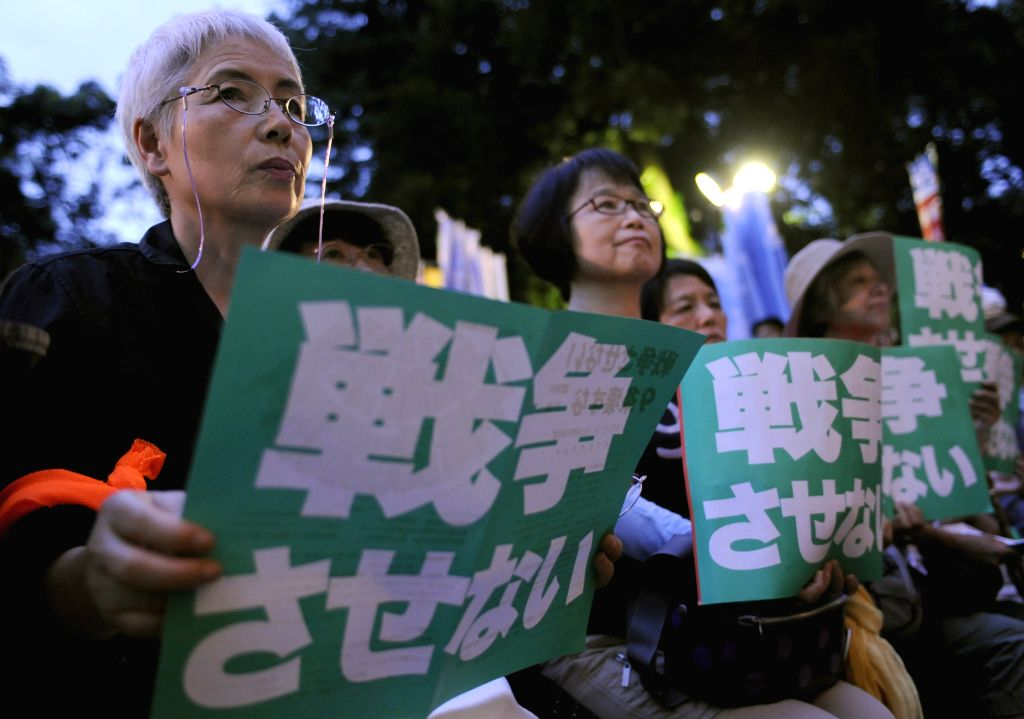 "People hold placards saying ""we won't let Japan go to wars"" during a protest against Abe cabinet's policy to ease the limit of the country's pacifist ..."
