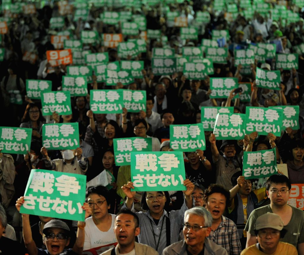 "People shout slogans and hold placards saying ""we won't let Japan go to wars"" during a protest against Abe cabinet's policy to ease the limit of the ..."