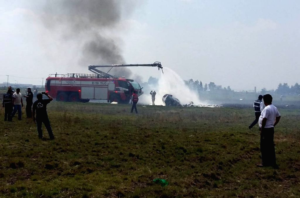 TOLUCA, May 18, 2017 - Photo taken with a mobile phone shows fire fighters working at the site after a plane crashed near Toluca International Airport in Toluca, central Mexico, May 17, 2017. A small ...
