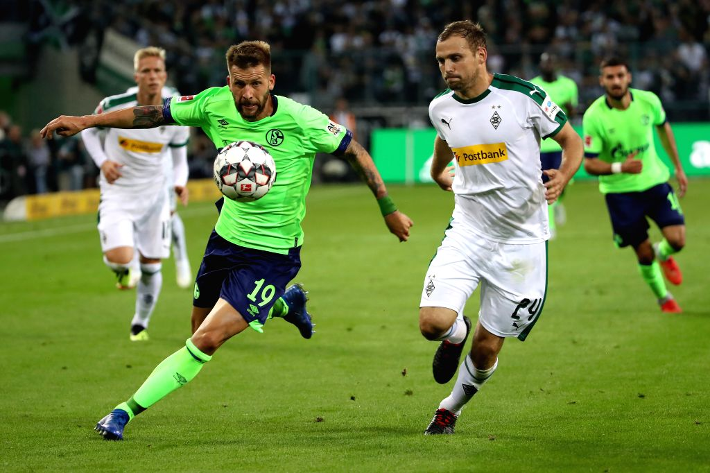 Tony Jantschke (R) of Borussia Moenchengladbach vies with Guido Burgstaller of FC Schalke 04 during the Bundesliga match between Borussia Monchengladbach ...