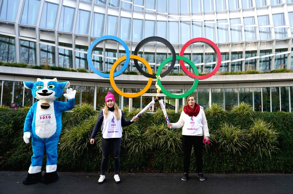 Torch bearer Aurore Locher (R) and Christelle Boivin pose for photos with mascot of Lausanne 2020, Yodli, during a torch relay for the 3rd Youth Winter Olympic ...