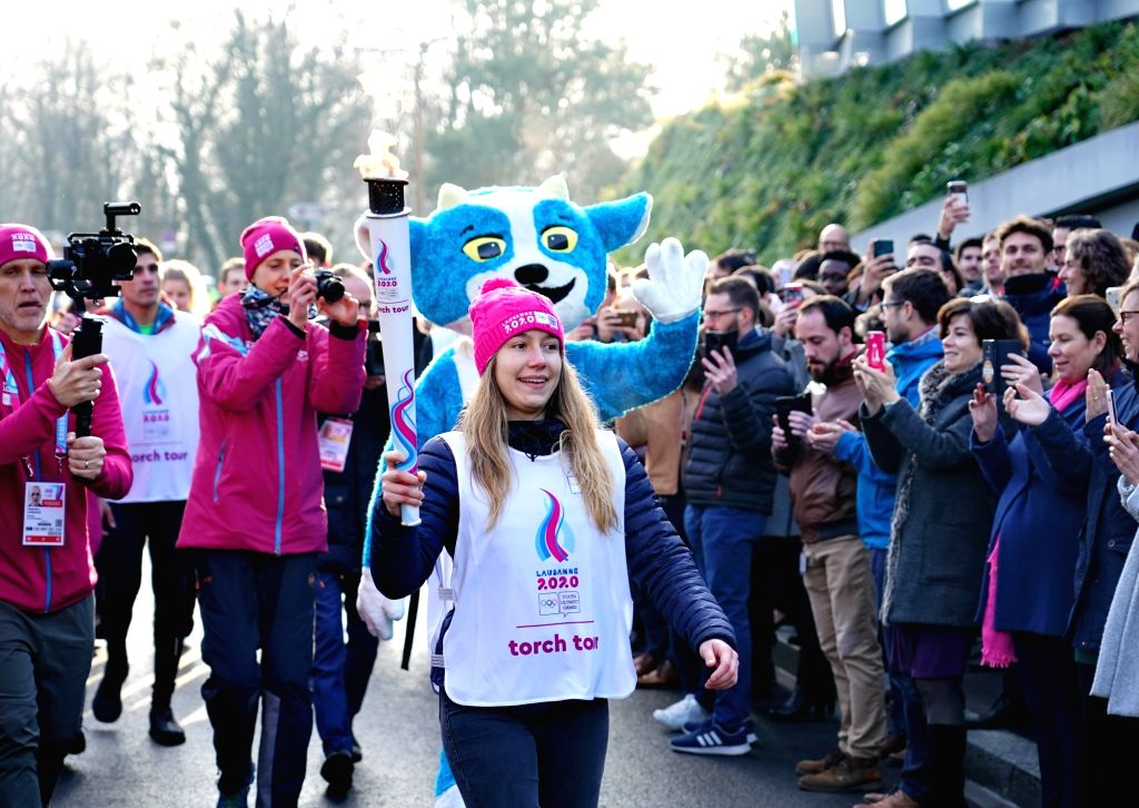 Torch bearer Christelle Boivin runs during a torch relay for the 3rd Youth Winter Olympic Games in Lausanne, Switzerland, Jan. 8, 2020.