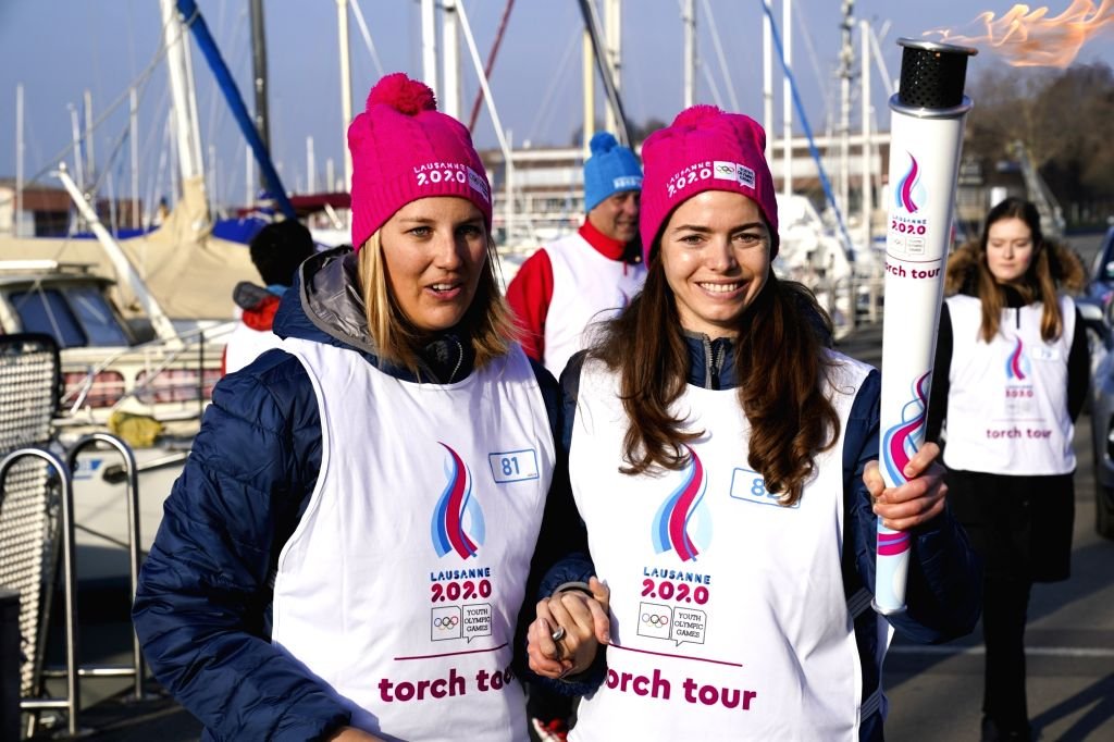 Torch bearer Louise Thilo (L) and Celine van Till pose for photos during a torch relay for the 3rd Youth Winter Olympic Games in Lausanne, Switzerland, Jan. 8, 2020.