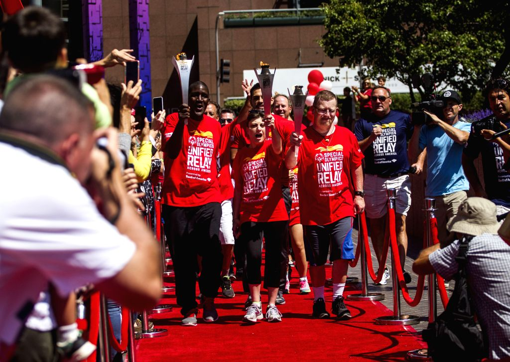 Torch bearers carrying the torch arrive in downtown Los Angeles for the Special Olympics Unified Relay Across America on July 10, 2015. The Los Angeles will ...