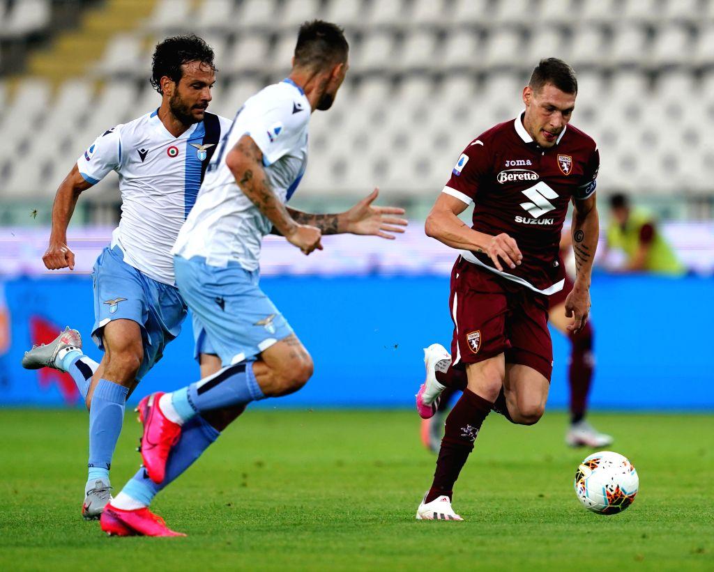 Torino's Andrea Belotti (R) vies with Lazio's Marco Parolo (L) during a Serie A football match between Torino and Lazio in Turin, Italy, June 30, 2020.