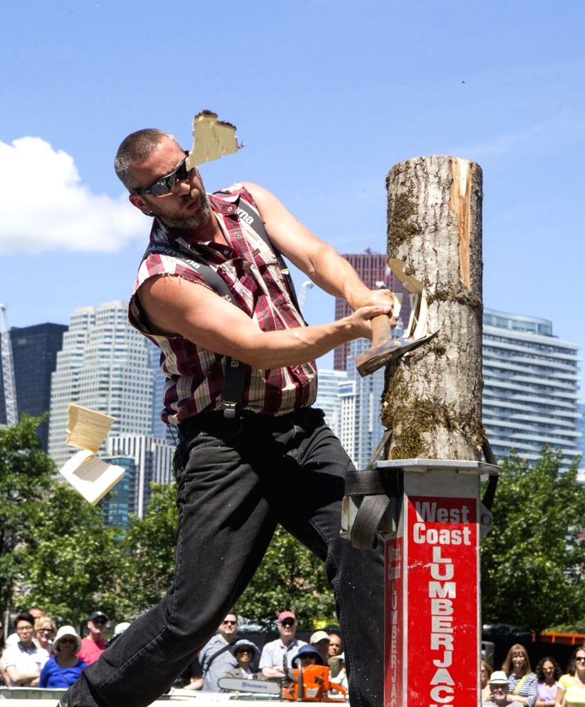 Toronto : A lumberjack uses an axe to chop wood during the Lumberjack Show at the 2017 Toronto Redpath Waterfront Festival in Toronto, Canada, on July 3, 2017. Featuring log rolling, axe throwing and ...