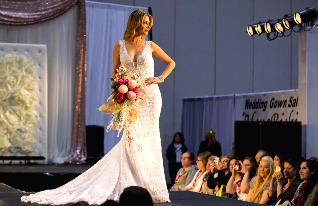 A model presents a wedding dress during the fashion show of the 2015 Toronto's Bridal Show at the Exhibition Place in Toronto, Canada, April 11, 2015. (Xinhua/Zou ...