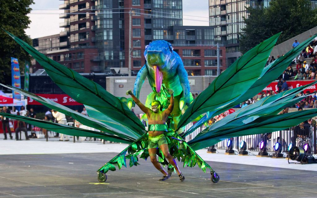 A dressed up competitor perfroms with his float during the King and Queen Competition and Show of the 47th Toronto Caribbean Carnival in Toronto, Canada, July 31, ...