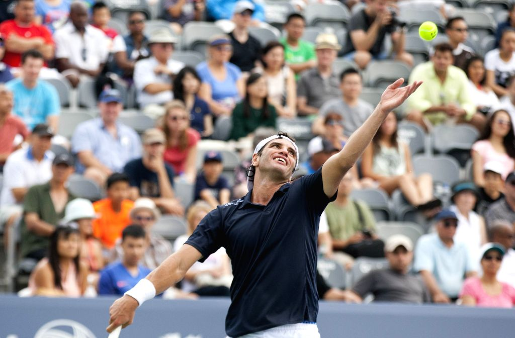Malek Jaziri of Tunisia serves during the first round of men's singles qualifying match against Filip Peliwo of Canada at the 2014 Rogers Cup in Toronto, Canada, ...