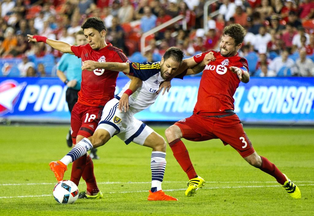 TORONTO, Aug. 4, 2016 - Marky Delgado (L) and Drew Moor (R) of Toronto FC vie with Juan Manuel Martinez of Real Salt Lake during their 2016 Major League Soccer (MLS) match in Toronto, Canada, Aug. 3, ...