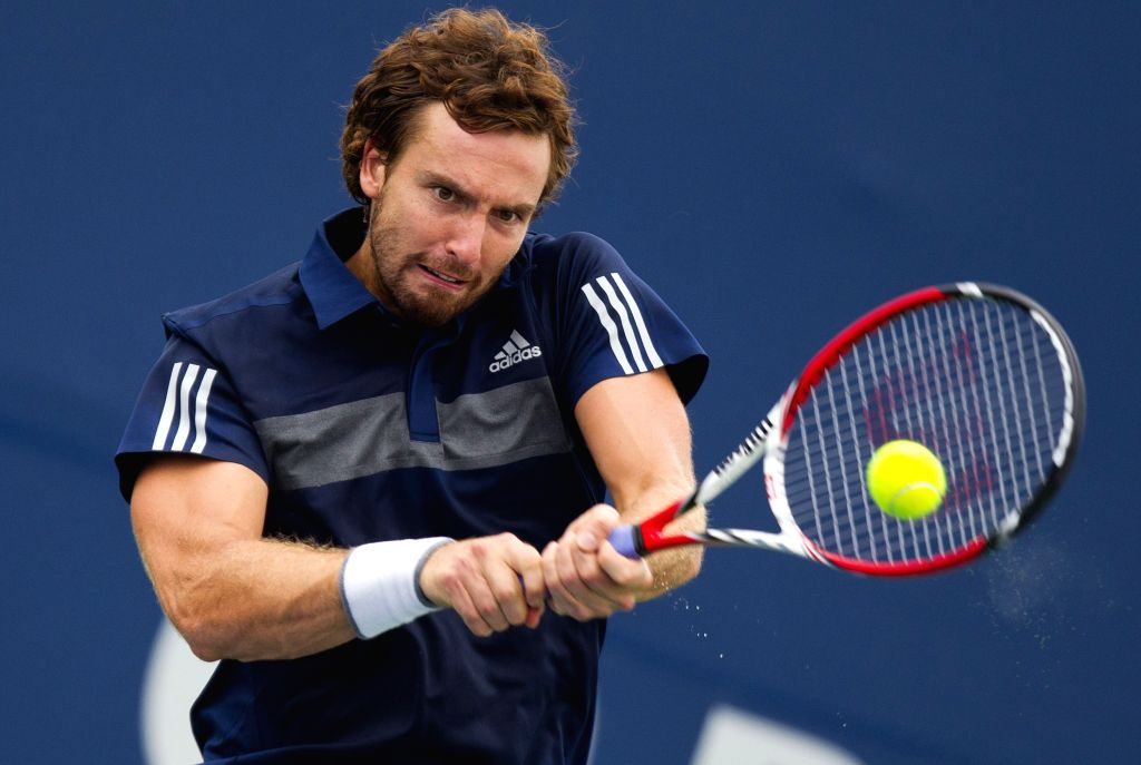Ernests Gulbis of Latvia returns the ball during the first round of men's singles against Joao Sousa of Portugal at the 2014 Rogers Cup in Toronto, Canada, Aug. 5, ...