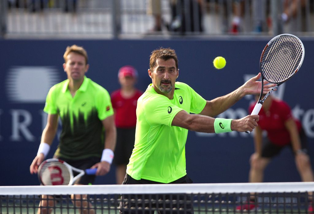 Daniel Nestor(L) of Canada and Nenad Zimonjic of Serbia compete during the second round of men's doubles against Novak Djokovic(L) of Serbia and Stan Wawrinka of ...