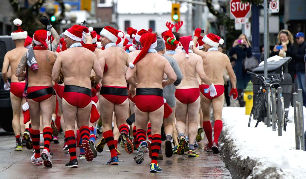 Participants in red bathing suits run during the 2014 Toronto Santa Speedo Run event in Toronto, Canada, Dec. 13, 2014. Dozens of participants took part in this ...