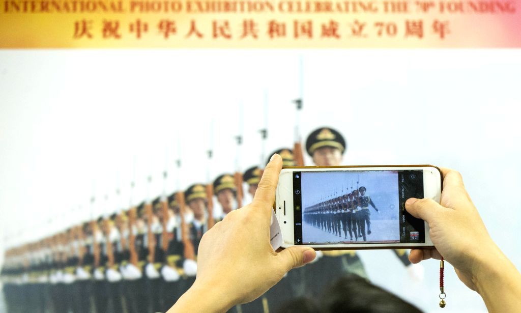 TORONTO, Dec. 7, 2019 - A visitor takes pictures at a photo exhibition marking the 70th anniversary of the founding of the People's Republic of China (PRC) in Scarborough of Greater Toronto Area, ...