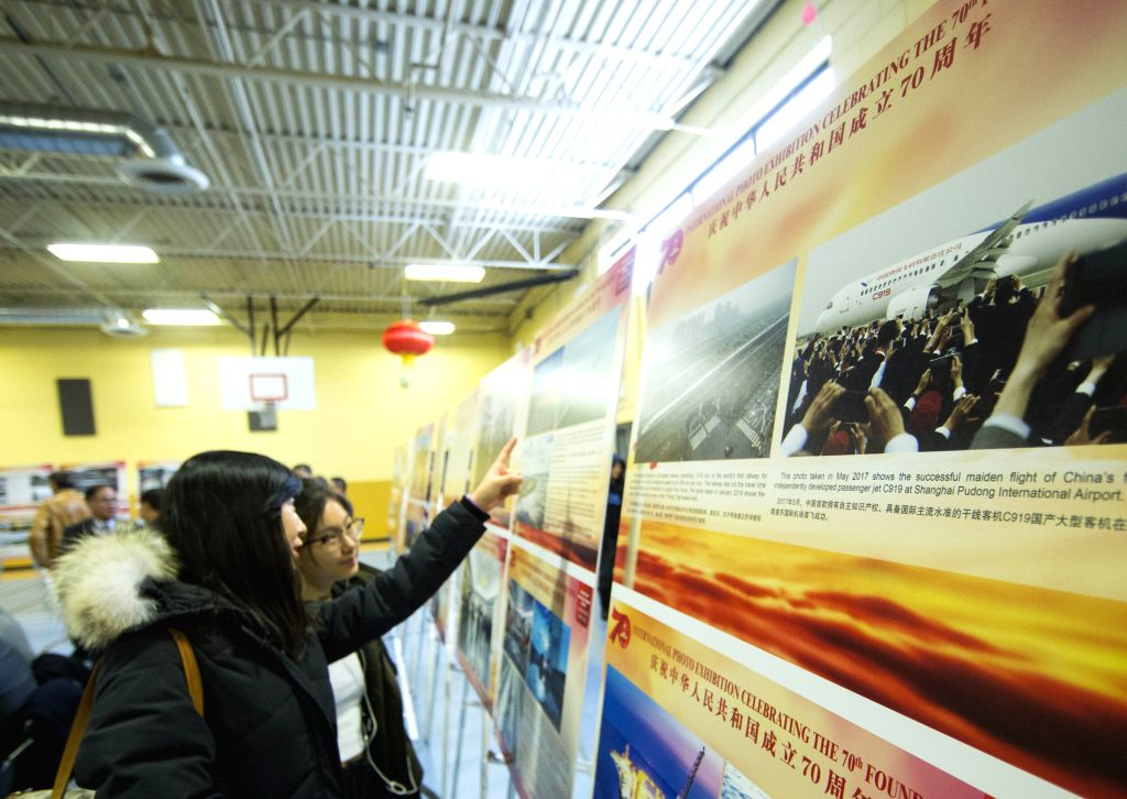 TORONTO, Dec. 7, 2019 - Visitors view pictures at a photo exhibition marking the 70th anniversary of the founding of the People's Republic of China (PRC) in Scarborough of Greater Toronto Area, ...