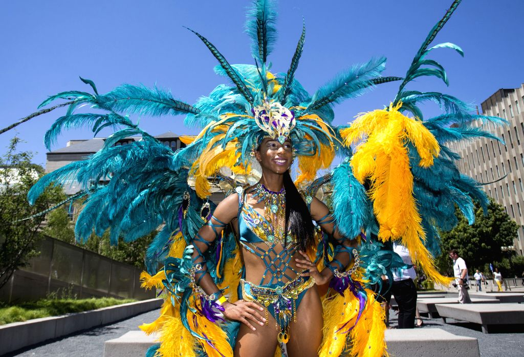 TORONTO, July 10, 2018 - A reveller poses for photos during the official launch ceremony of the 2018 Toronto Caribbean Carnival at Nathan Philips Square in Toronto, Canada, July 10, 2018. As an ...