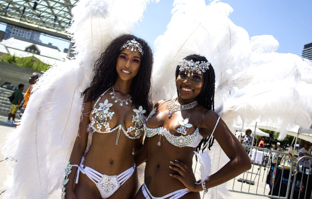 TORONTO, July 10, 2018 - Revellers pose for photos during the official launch ceremony of the 2018 Toronto Caribbean Carnival at Nathan Philips Square in Toronto, Canada, July 10, 2018. As an ...