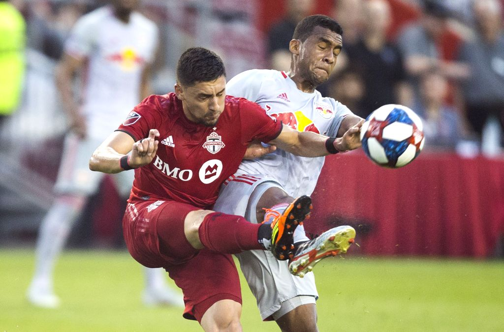 TORONTO, July 18, 2019 - Marco Delgado(L) of Toronto FC vies with Cristian Casseres Jr. of New York Red Bulls during their 2019 Major League Soccer(MLS) match at BMO Field in Toronto, Canada, July ...