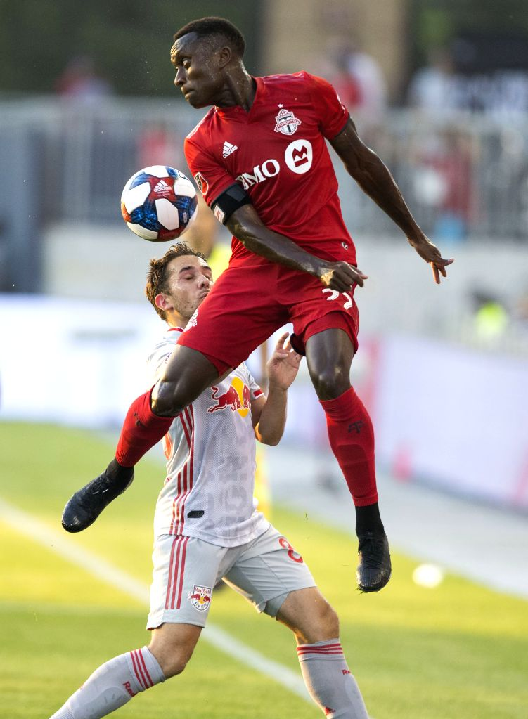TORONTO, July 18, 2019 - Richie Laryea(Front) of Toronto FC vies with Vincent Bezecourt of New York Red Bulls during their 2019 Major League Soccer(MLS) match at BMO Field in Toronto, Canada, July ...
