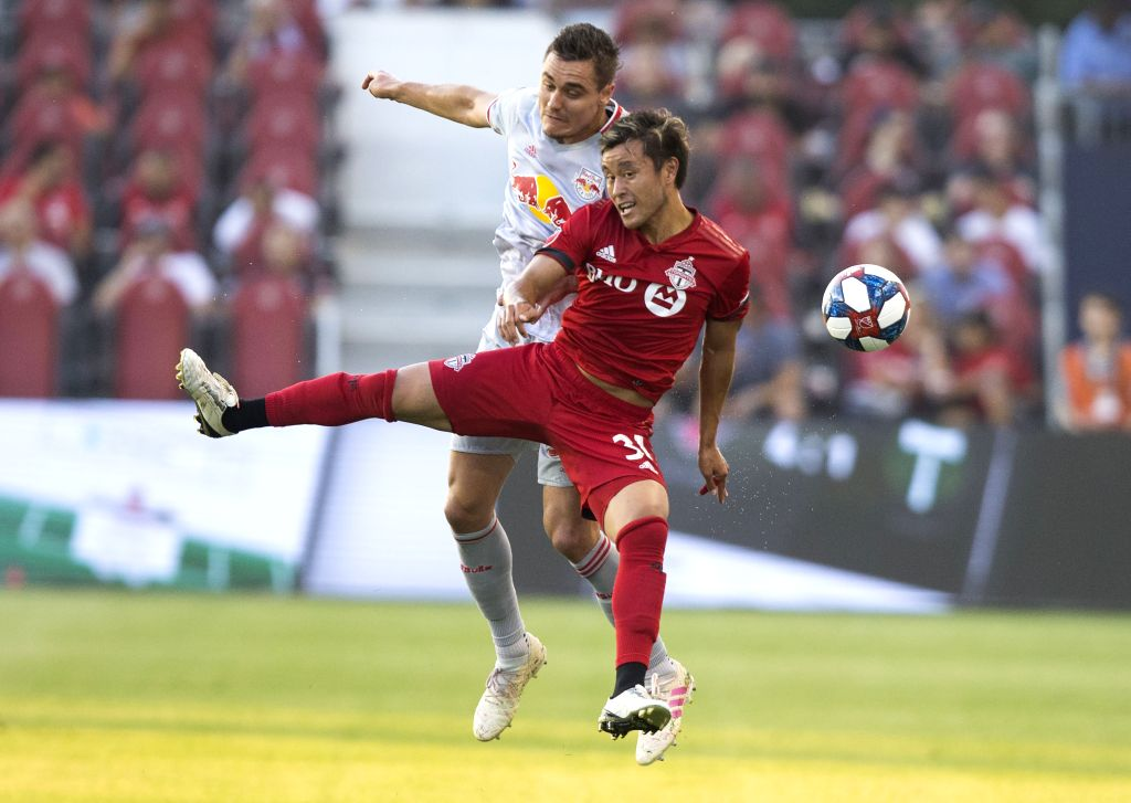 TORONTO, July 18, 2019 - Tsubasa Endoh(Front) of Toronto FC vies with Aaron Long of New York Red Bulls during their 2019 Major League Soccer(MLS) match at BMO Field in Toronto, Canada, July 17, 2019. ...