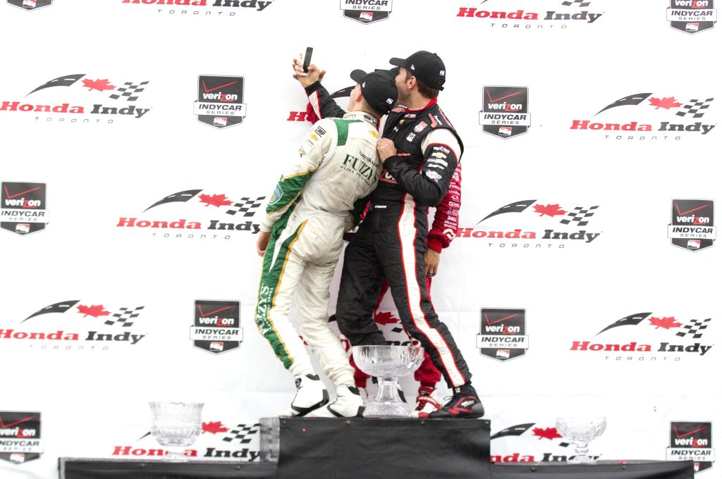 Ed Carpenter Racing's British driver Mike Conway (L) takes a selfie with Tony Kanaan (C) of Target Chip Ganassi Racing and Will Power of Team Penskecelebrates ...