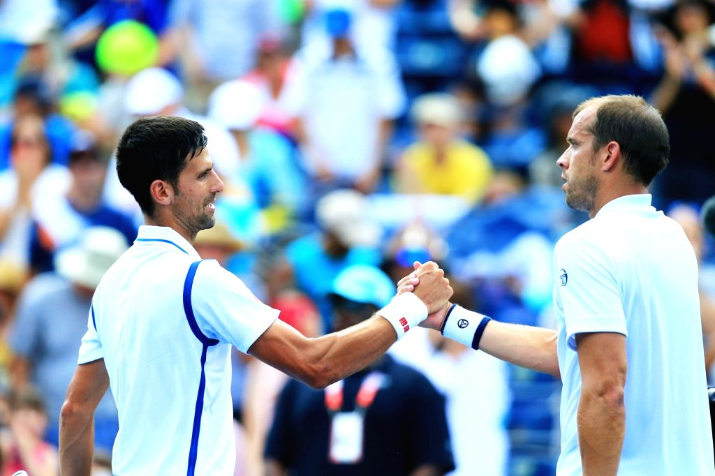 TORONTO, July 28, 2016 - Novak Djokovic (L) of Serbia shakes hands with Gilles Muller of Luxembourg after their second round of men's singles match at the 2016 Rogers Cup in Toronto, Canada, July 27, ...