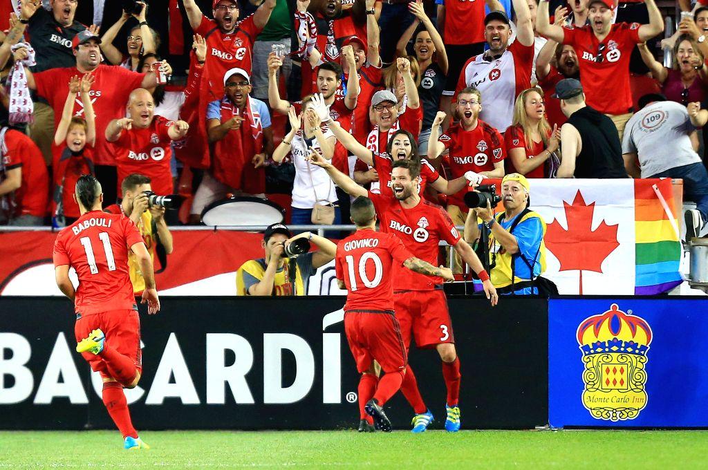 TORONTO, June 19, 2016 - Drew Moor(R-1sd) of Toronto FC celebrates scoring with teammate Sebastian Giovinco(R-2nd) during the 2016 Major League Soccer (MLS) match against LA Galaxy in Toronto, ...