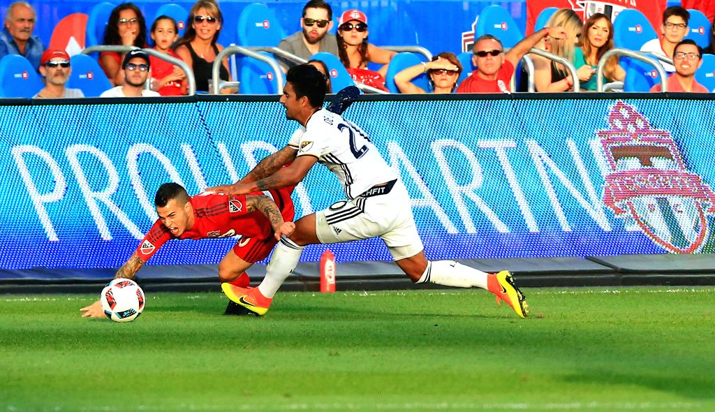 TORONTO, June 19, 2016 - Sebastian Giovinco(L) of Toronto FC vies with A.J. DeLaGarza of LA Galaxy during their 2016 Major League Soccer (MLS) match in Toronto, Canada, June 18, 2016. Toronto FC won ...