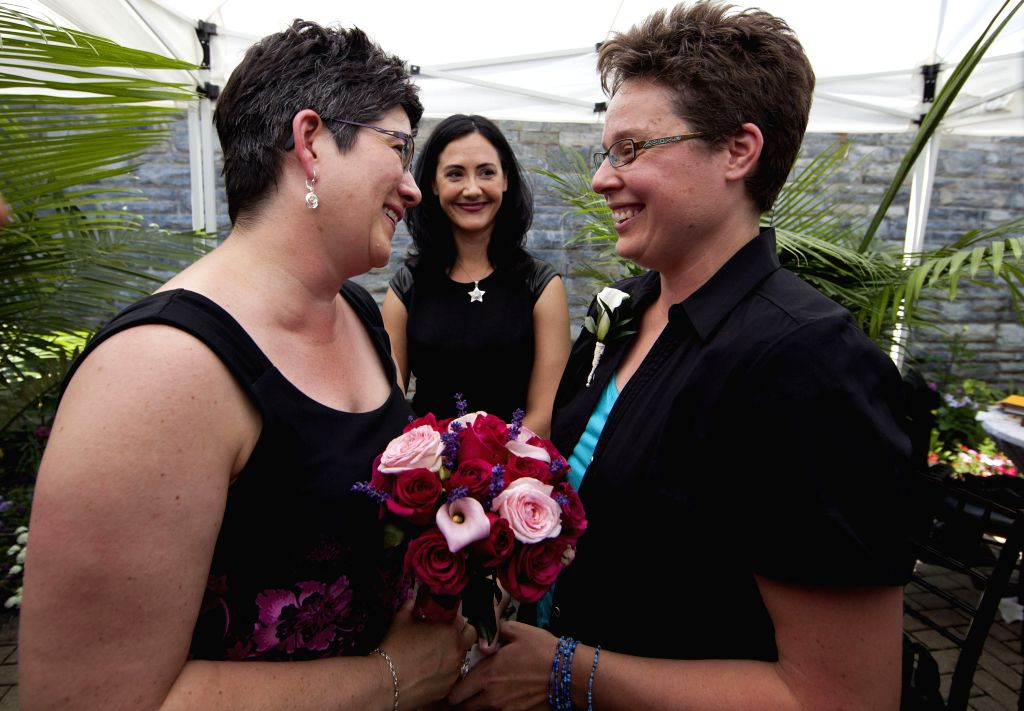 A couple exchange their vows during a LGBTQ mass wedding at Casa Loma in Toronto, Canada, June 26, 2014. A total of 110 LGBTQ  couples from around the world were ...