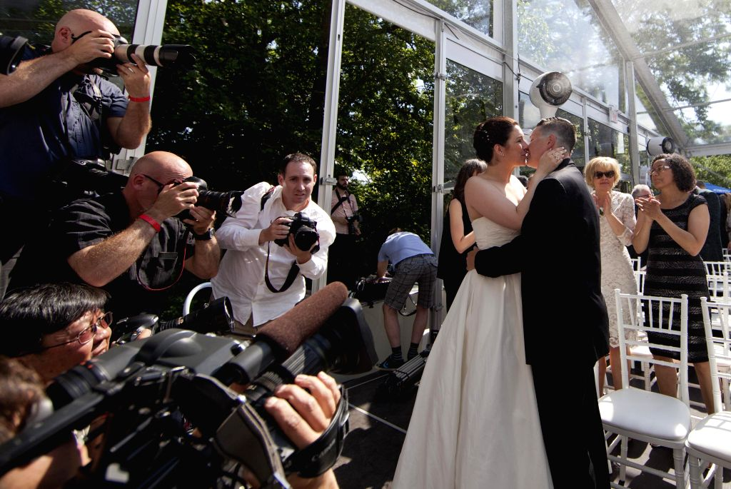 A couple (R) pose for photos during a LGBTQ mass wedding at Casa Loma in Toronto, Canada, June 26, 2014. A total of 110 LGBTQ  couples from around the world were ...