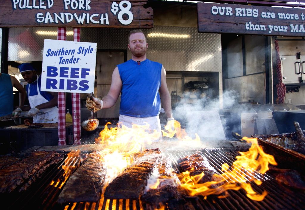 A man barbecues ribs during the 15th Annual Toronto Ribfest in Toronto, Canada, June 27, 2014. Kicked off on Friday, the five-day meat-lover's fesitival is expected