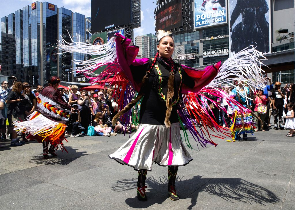 TORONTO, June 29, 2017 - Performers wearing women's traditional costume dance before the fashion show of the 2017 Aboriginal History Month Celebration at Yonge-Dundas Square in Toronto, Canada, June ...