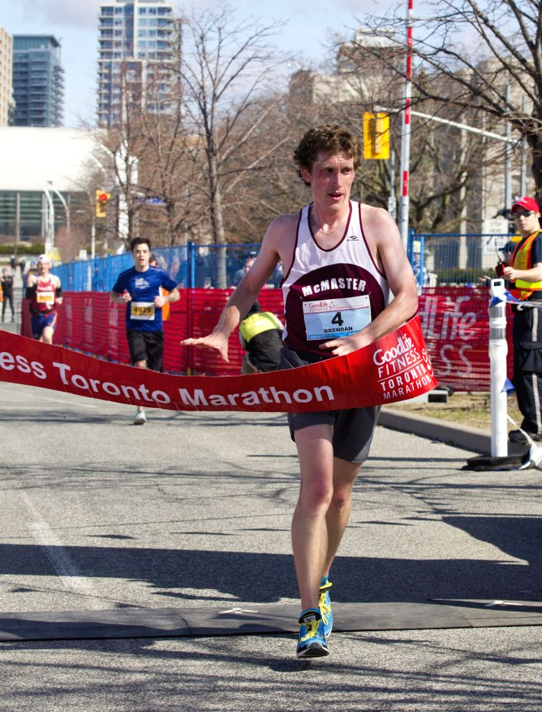 Brendan Kenny of Canada runs across the finish line to win men's marathon during the 2014 Toronto Marathon inToronto, Canada, May 4, 2014. About 15,000 runners from ..
