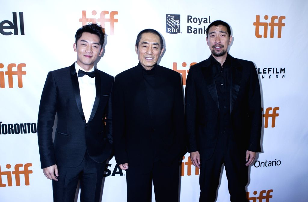 """TORONTO, Sept. 11, 2018 - Director Zhang Yimou (C), actor Zheng Kai (L) and Wang Qianyuan pose for photos before the North American premiere of the film """"Shadow"""" at Roy Thomson Hall during ... - Zheng Kai"""