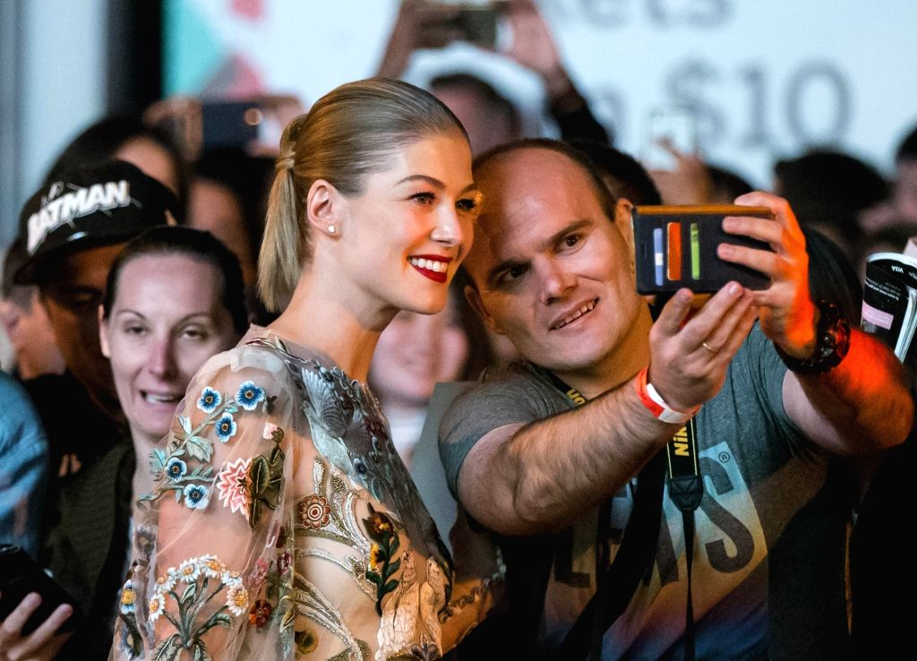 "TORONTO, Sept. 12, 2017 - Actress Rosamund Pike (L) poses for photos with a fan before the premiere of film ""Hostiles"" at Princess of Wales Theatre during the 2017 Toronto International ... - Rosamund Pike"