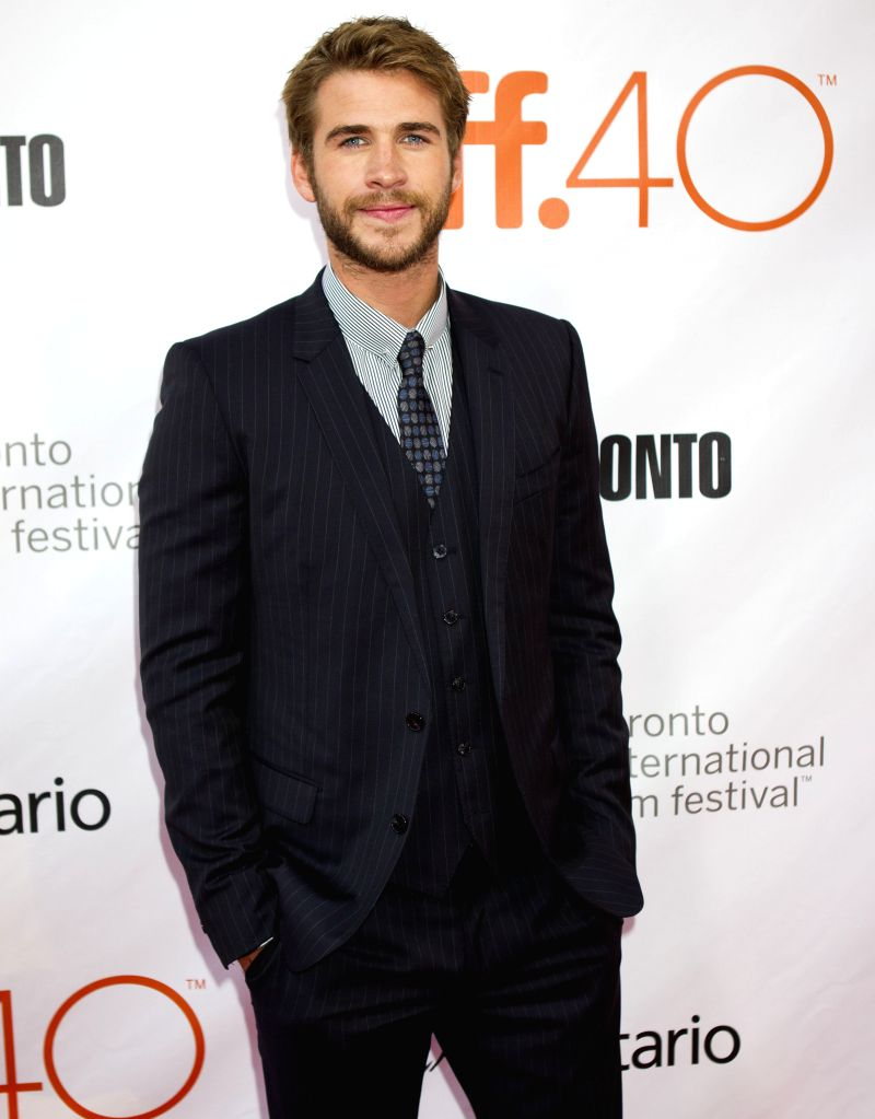 """TORONTO, Sept. 15, 2015 (Xinhua) -- Actor Liam Hemsworth poses for photos before the world premiere of the film """"The Dressmaker"""" at Roy Thomson Hall during the 40th Toronto International Film Festival in Toronto, Canada, Sept. 14, 2015. (Xinhua/Zou Z - Liam Hemsworth"""