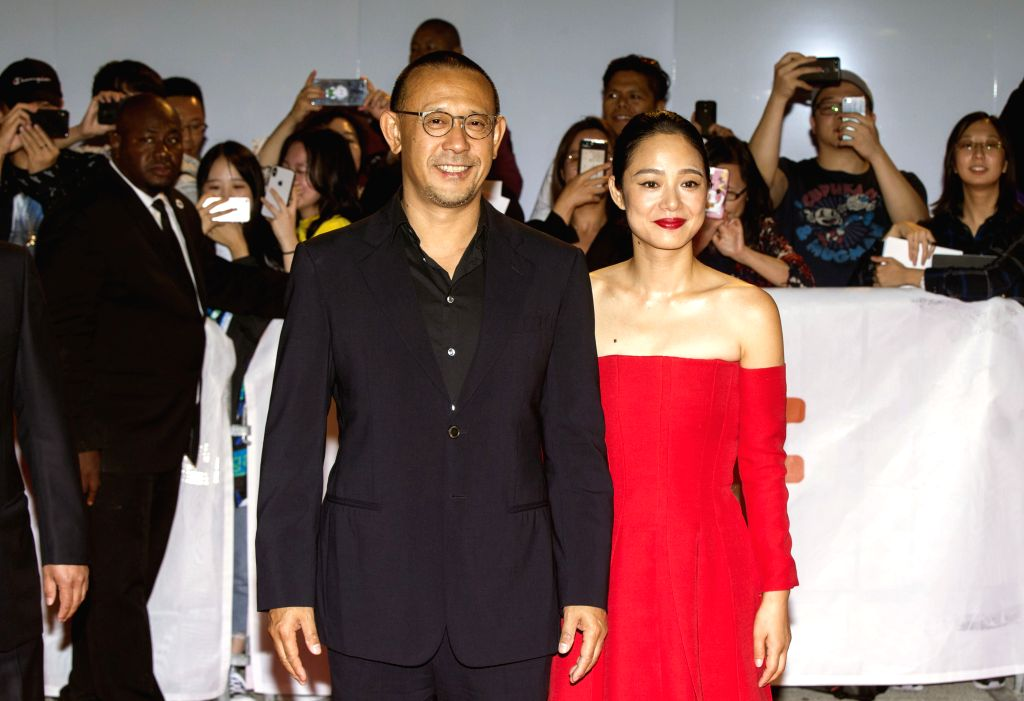 """TORONTO, Sept. 15, 2018 - Director Jiang Wen (L) and actress Zhou Yun pose for photos before the film """"Hidden Man"""" at Roy Thomson Hall during the 2018 Toronto International Film Festival in ... - Zhou Yun"""