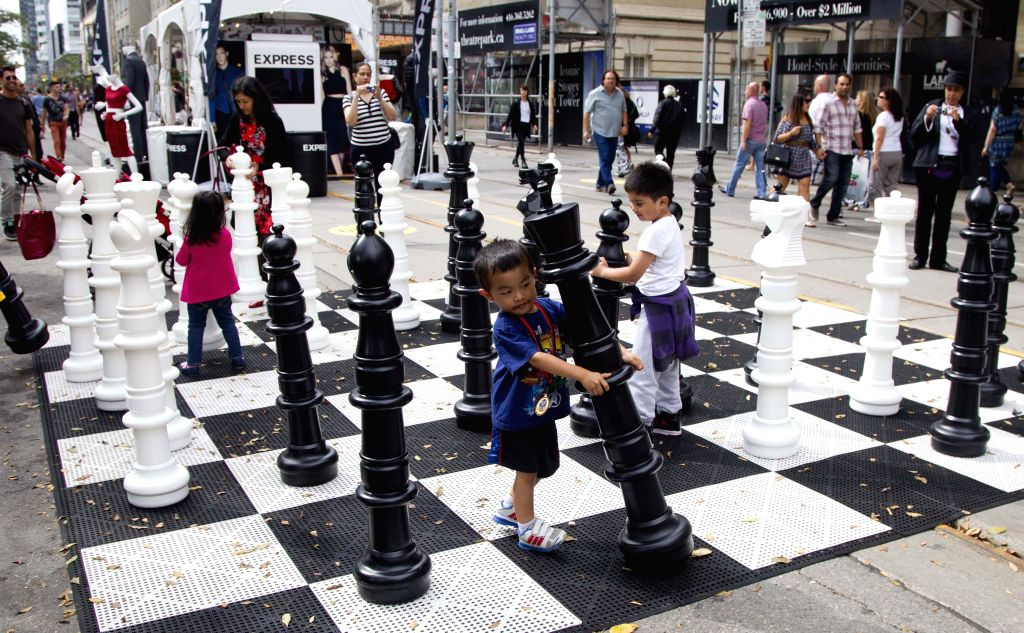 Children play with chess at the pedestrian mall of the 39th Toronto International Film Festival in Toronto, Canada, on Sept. 6, 2014.