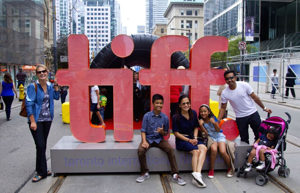 Visitors pose for photos with the symbol of the Toronto International Film Festival at the pedestrian mall of the 39th Toronto International Film Festival in ...