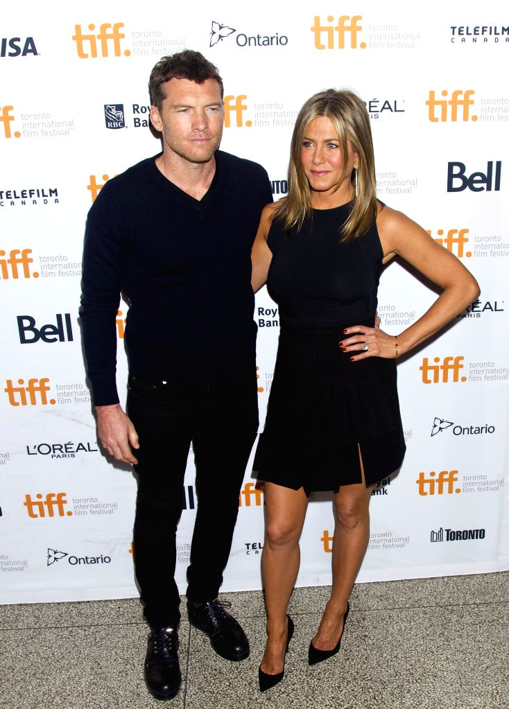 "Actor Sam Worthington (L) and actress Jennifer Aniston pose for photos before the premiere of the film ""Cake"" at Elgin Theatre during the 39th Toronto ... - Sam Worthington"
