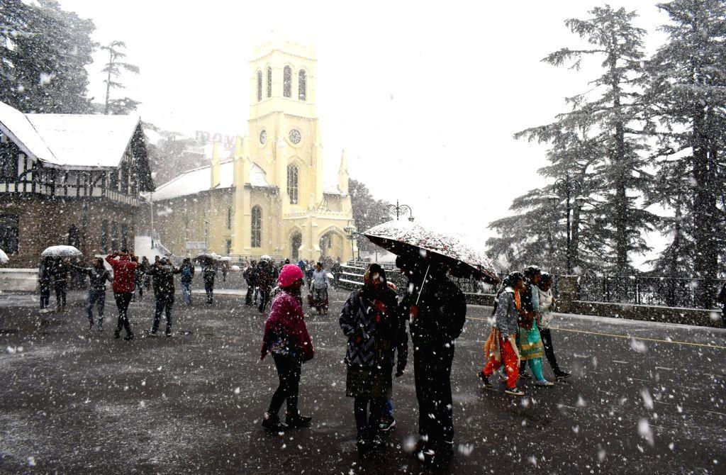 Tourists enjoy first snowfall of the season in Shimla on Dec 12, 2018.